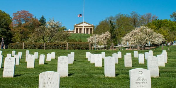 rows on grave stones in the foreground and Arlington House and flag at half mast in the background