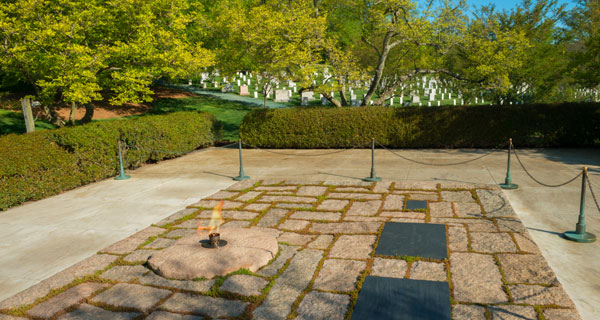 view of John F Kennedy gravesite featuring plaques on the ground accompanied by an eternal flame