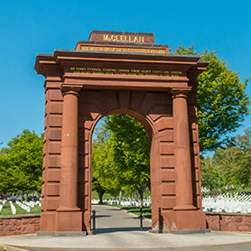 picture of a tall gate that reads 'McClellan' at the top and trees and headstones in the background