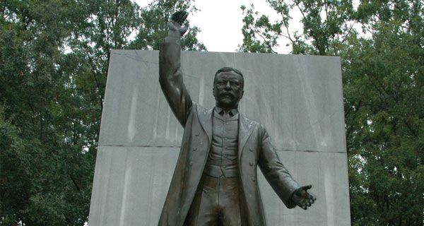 Statue of Theodore Roosevelt from the waist up and a large stone behind it