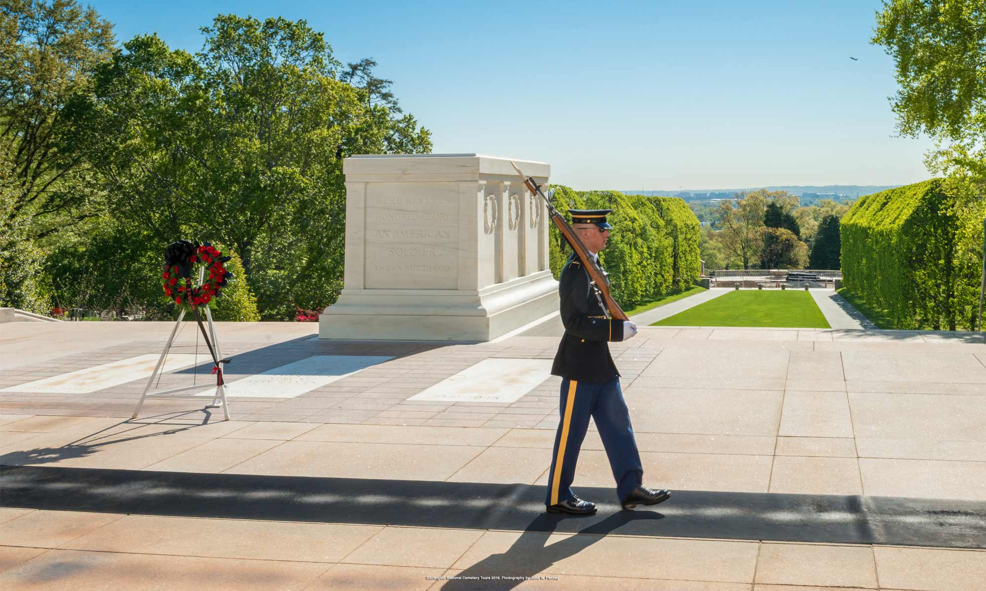 Guard standing guard in front of a large above ground tomb dedicated to unknown soldiers at Arlington National Cemetery