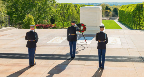 Three guards saluting and standing guard in front of a large above ground tomb dedicated to unknown soldiers at Arlington National Cemetery
