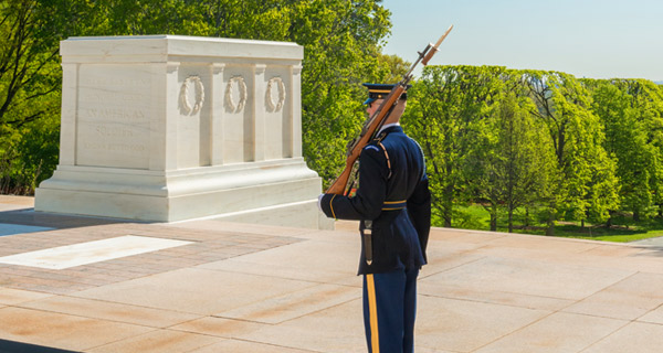 guard at tomb of unknown soldier standing watch in front of a large tomb above ground