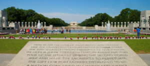 View of Washington DC World War II Memorial featuring a large stone inscription in foreground, a large fountain in the middle, and large columns surrounding fountain with flower bouquets surrounding monument and the Lincoln Memorial in background