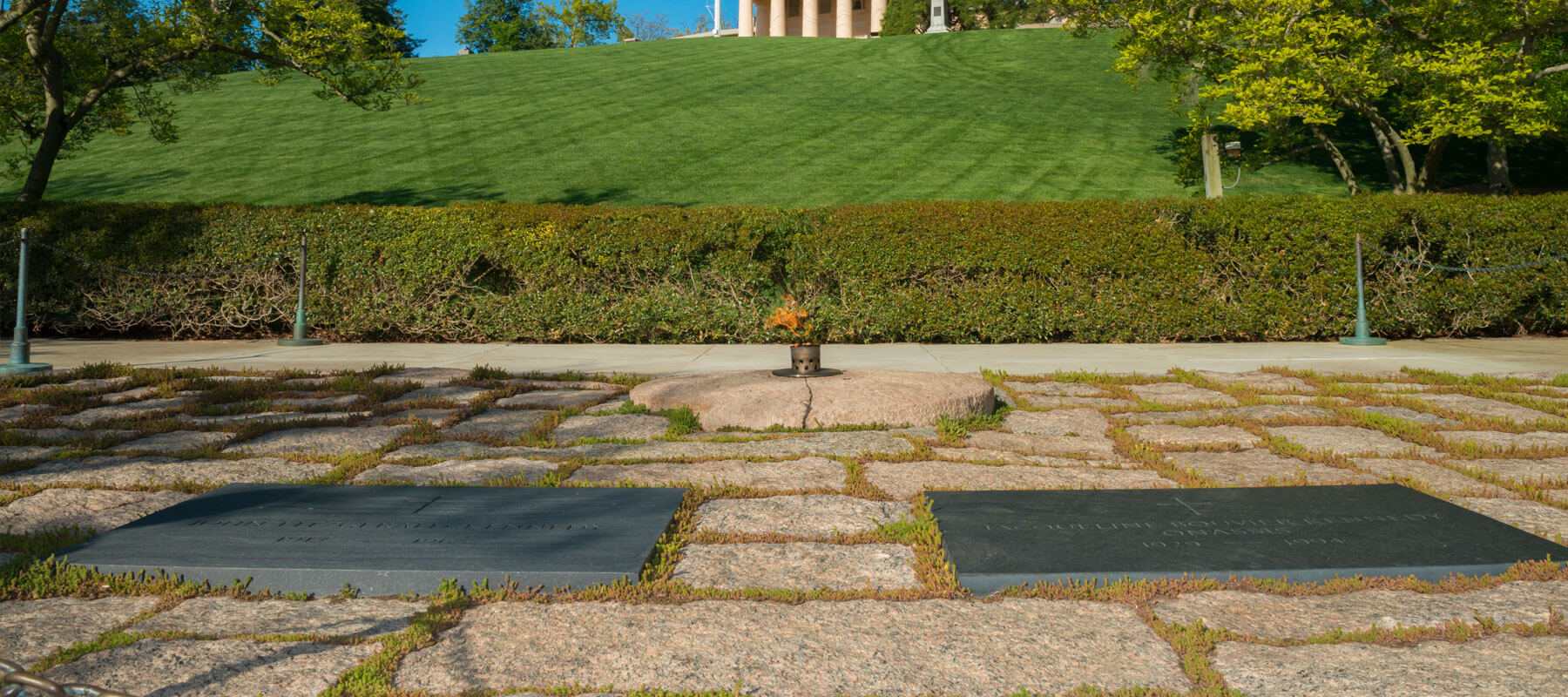 front view of John F Kennedy gravesite marked by two plaques on the ground and an eternal flame in front of plaques
