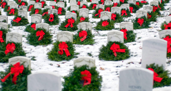 holiday wreaths across Arlington national cemetery gravestones with snow covering the ground