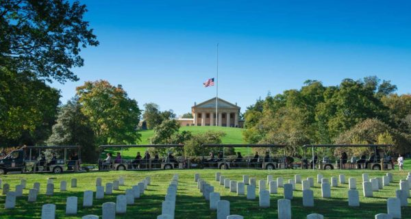 Arlington National Cemetery Tours vehicle driving past rows of gravestones in the foreground and Arlington House and US flag on pole in the background